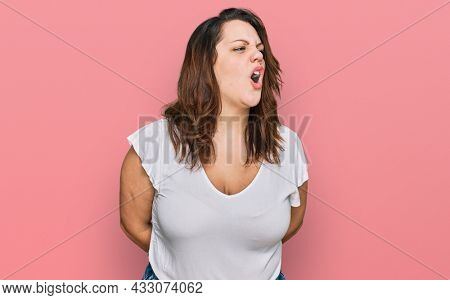 Young plus size woman wearing casual white t shirt angry and mad screaming frustrated and furious, shouting with anger. rage and aggressive concept.