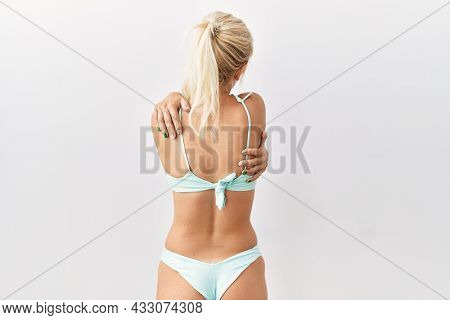 Young caucasian woman wearing bikini over isolated background hugging oneself happy and positive from backwards. self love and self care