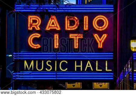 Radio City Music Hall Marquee Neon Sign In Nyc Near Silhouette Tree Leavs. The Focus Is On The Marqu