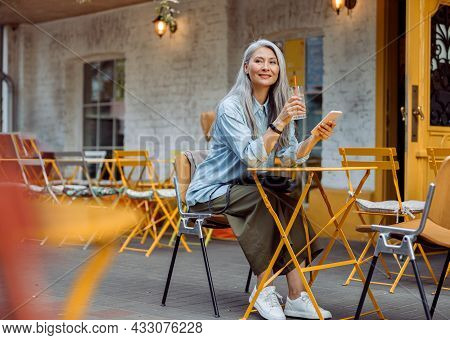Grey Haired Asian Woman With Glass And Smartphone On Outdoors Cafe Terrace