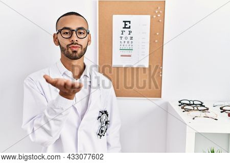 African american optician man standing by eyesight test looking at the camera blowing a kiss with hand on air being lovely and sexy. love expression.