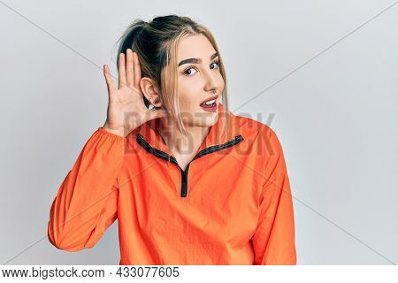 Young modern girl wearing sports sweatshirt smiling with hand over ear listening an hearing to rumor or gossip. deafness concept.