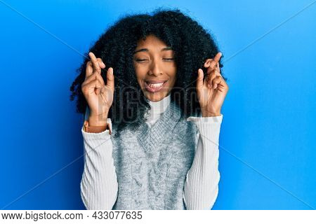 African american woman with afro hair wearing casual winter sweater gesturing finger crossed smiling with hope and eyes closed. luck and superstitious concept.