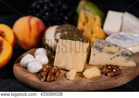 Various Types Of Cheese On A Dark Background. Nearby Are Peaches, Grapes, Nuts. An Exquisite Delicac