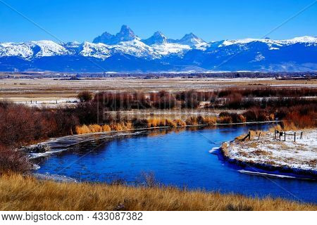 Grand Teton Mountain Range with curving blue river in snow with sky