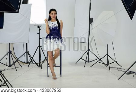 Young Asian Model Posing In  White Photography Scene. The Atmosphere In The Photo Studio With A Comp