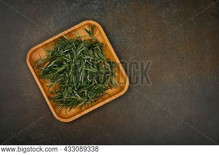 Close Up Fresh Green Rosemary Leaves On Bamboo Wooden Plate On Table, Elevated Top View, Directly Ab