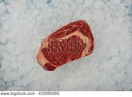 Close Up One Aged Prime Marbled Raw Ribeye Beef Steak On Background Of Crushed Ice On Retail Display