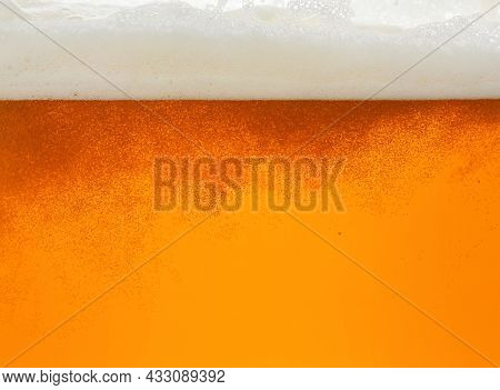 Close Up Background Texture Of Lager Beer With Bubbles And Froth, Pouring In Glass, Low Angle, Side