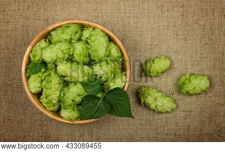 Close Up One Wooden Bowl Of Fresh Green Hop Flowers On Brown Jute Canvas Background, Elevated Top Vi