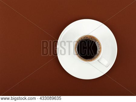 Close Up One White Cup Full Of Black Coffee On Saucer Over Brown Paper Background, Elevated Top View