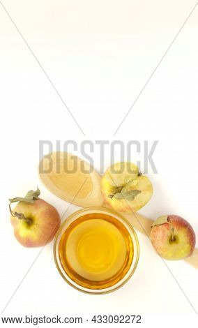 Two Apples With Leaves, A Half Of Apple With Green Leaf, Bowl With Apple Cider Vinegar And Wooden Sp