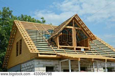 Gable Roofing Construction And Framing. An Incomplete Concrete Block House Construction With Timber