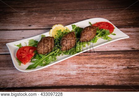 Traditional Kebbe And Pita Bread On Big Round Plate In Lebanese Restaurant. High Quality Photo