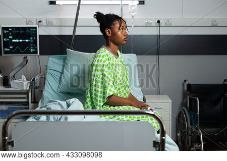 Young African American Person Sitting On Hospital Ward Bed With Fever, Sickness, Disease. Sick Teena