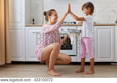 Side View Photo Of Cheerful Charming Mommy And Small Kid Giving High-five In Light Kitchen, Baking D