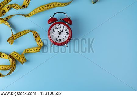 Weight Loss, Diet Concept, Alarm Clock And Tape Measure, Web Banner With Copy Space. Top View Of Red