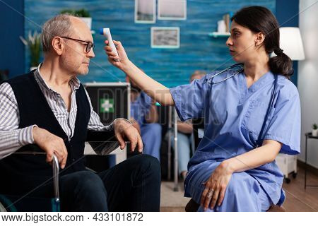 Support Assistant Worker Measuring Disabled Senior Man Temperature Using Medical Infrared Thermomete