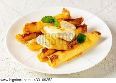 Blintz, Rolled Filled With Sweetened Cottage Cheese Pancakes Or Crepes On A White Plate On A Wooden