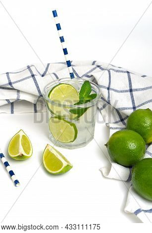 Cut Lime And Lime Water Into Baking Soda In A Glass With A Straw. Refreshing Shot On A White Backgro