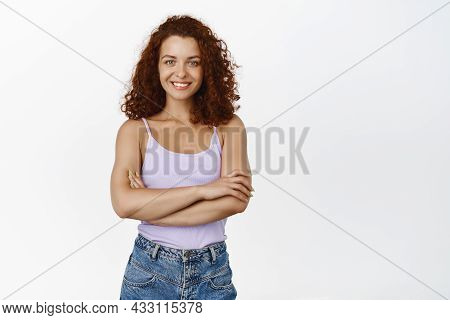 Portrait Of Fit And Stylish Confident Girl With Red Curly Hair, Cross Arms On Chest And Looking Conf