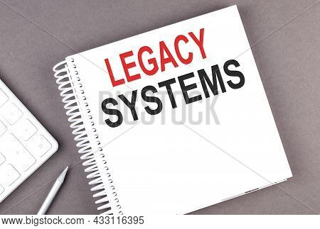 Legacy Systems Text On Notebook With Calculator And Pen