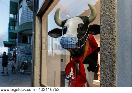 Porto, Portugal - September 7, 2021: A Statue Of A Masked Cow Outside A Shop In Downtown Porto, Port
