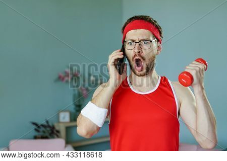 Portrait Of Funny Surprised Geek Talking On The Phone While Exercising With Dumbbell