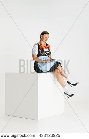 One Pretty Woman, Waitress In Traditional Austrian Or Bavarian Costume Sitting On Huge Box Isolated