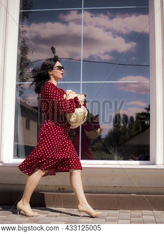 Happy Grocery Shopper. Portrait Of Beautiful Traditional White Woman In Red Dress Holding Paper Shop