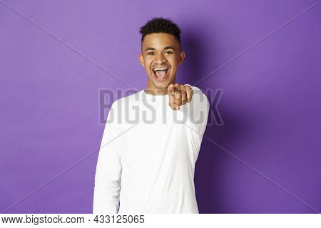 Image Of Handsome Young African-american Man In White Sweatshirt, Pointing Finger At Camera And Smil