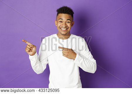 Image Of Handsome African-american 20s Guy In White Sweatshirt, Pointing Fingers Left And Smiling, S