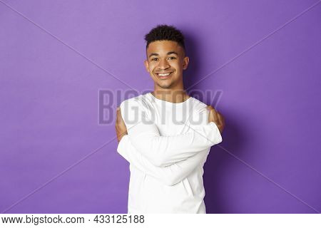Cheerful African-american Man In White Sweatshirt, Embracing Himself And Smiling, Standing Happy Ove