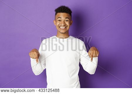 Portrait Of African-american Happy Guy, Wearing White Sweatshirt, Pointing Fingers Down And Smiling