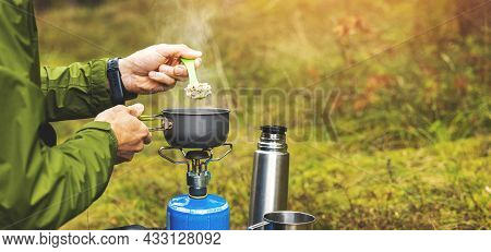 Preparing Food Outdoors On Gas Burner. Camping Cooking Equipment. Copy Space
