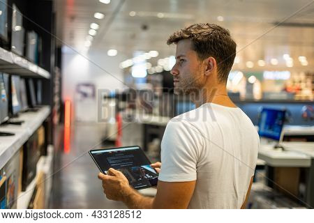 Side View Of Young Male Buyer Using Tablet To Compare Various Models Of Computer Monitors While Choo
