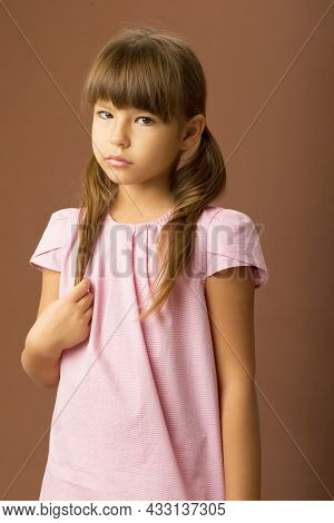 Close Up Side View Portrait Of Lovely Girl. Beautiful Child In Pink Blouse Looking Forward On Brown