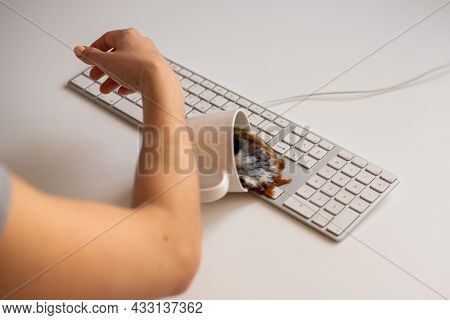Faceless Woman Typing On The Computer Spills A Cup Of Black Coffee On The Keyboard.