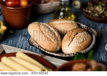closeup of some different bread buns on a table next to some plates with different ingredients to prepare vegan sandwiches or appetizers, such as some cooked baby corns, cherry tomatoes or avocado
