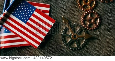 high angle view of some small flags of the United States, some clock hands and some cogwheels on a dark gray background, in a panoramic format to use as web banner or header
