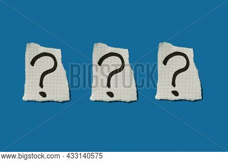 three question marks in three pieces of paper arranged in a line on a blue background