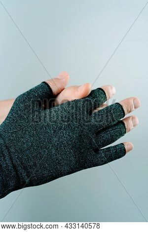 closeup of a caucasian man putting on or taking off a compression glove on an off-white background with some blank space on top