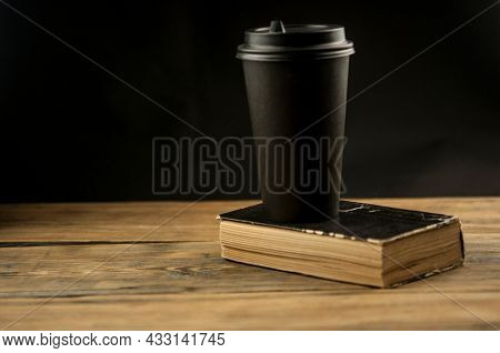 Old book and a cup of coffee in a disposable paper cup on a wooden table