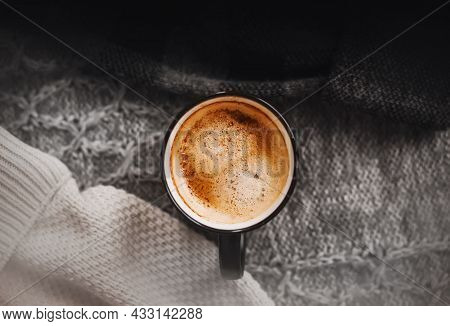 A Black Mug With A Fragrant Invigorating Latte Stands Among Warm Wool Sweaters Of Different Colors.