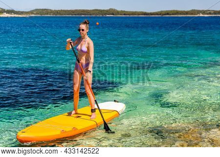 Young Girl Sup Board With A Paddle In Hand - Front View - The Calm Surface Of The Turquoise Sea, Cop