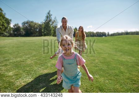 Joyful Cute Little Girl Looking Excited At Camera, Having Fun Together With Her Parents And Brother,