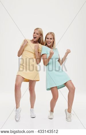 Young pleased european girls celebrating success or win. Pretty blonde girlfriends or sisters wearing green and yellow dresses and sneakers. Isolated on white background. Studio shoot. Copy space