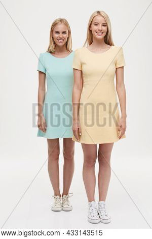 Front view of young smiling european girls standing and looking at camera. Pretty blonde girlfriends or sisters wear green and yellow dresses and sneakers. Isolated on white background. Studio shoot