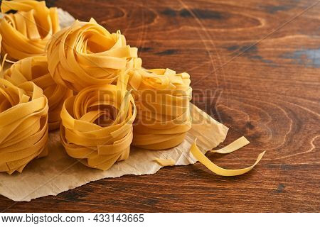 Homemade Tagliatelle Pasta In Brown Paper On An Old Wooden Background.