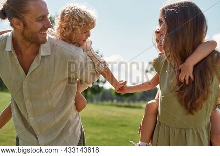 Little Kids, Boy And Girl Holding Each Other Hands While Enjoying Piggyback Ride On The Back Of Thei